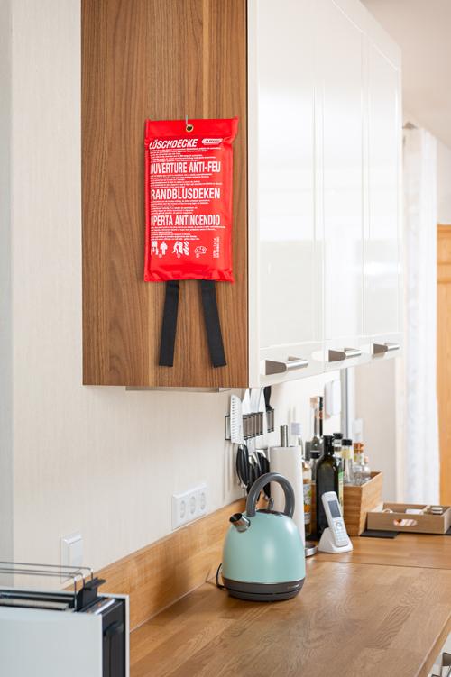 Feuerlöschdecke hängt an Schrank in der Küche