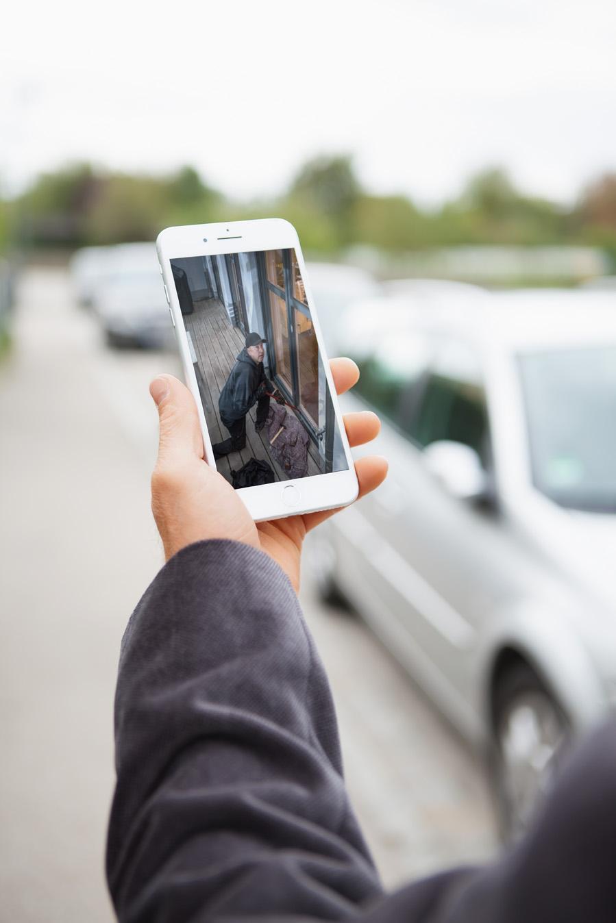 Eine Person hält ein Smartphone in der Hand auf dem man einen Einbrecher sieht