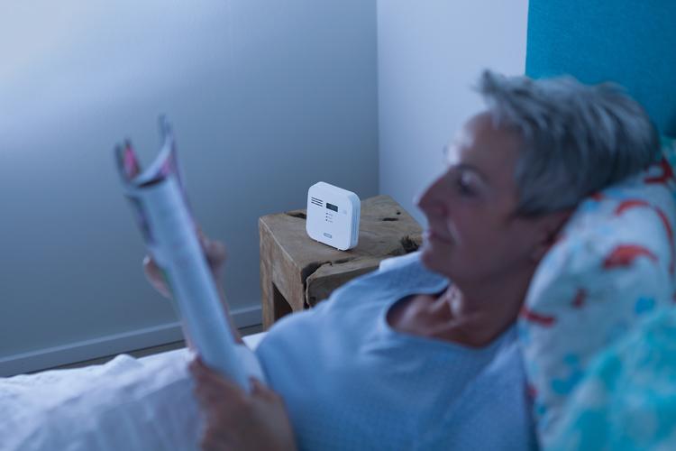 Frau liegt im Bett, auf dem Nachtschrank steht ein Warnmelder
