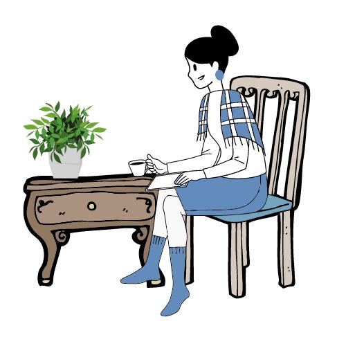 eine Frau in blauen Kompressionsstrümpfen mit dazu passendem Rock und Tuch sitzt am Tisch und trinkt etwas aus einer Tasse