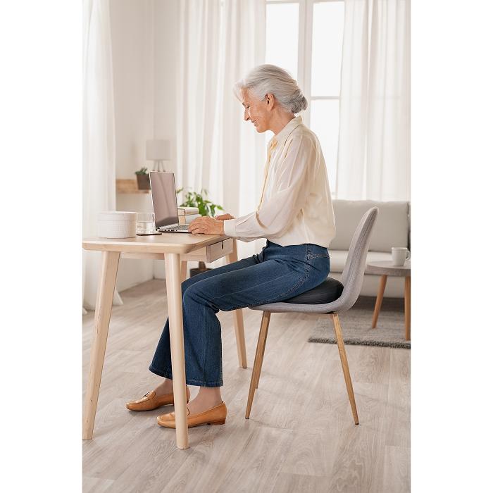 Eine Frau sitzt an einem Tisch auf einem Stuhl mit einem Balancekissen.