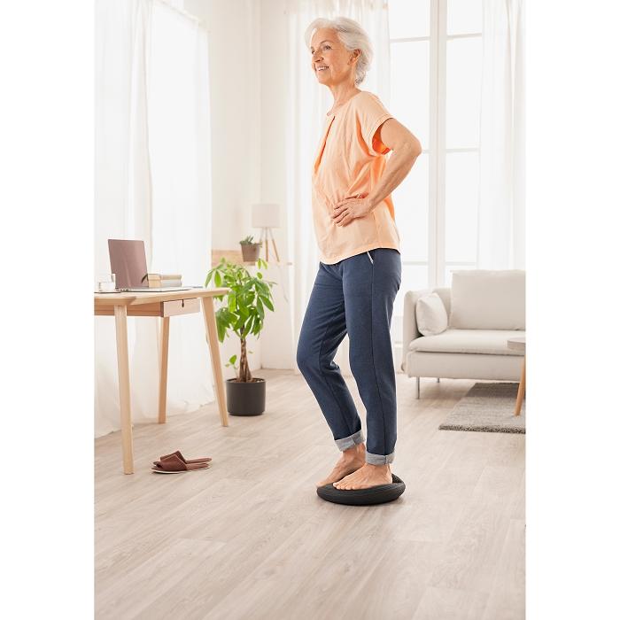 Eine Frau steht in einem Raum auf einem schwarzen Balancekissen.