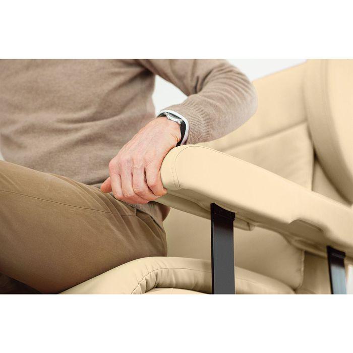 Eine Person verstellt gerade die Armlehne eines weißen Sessels. Sie hat eine hellbraune Hose an und ein Armband.