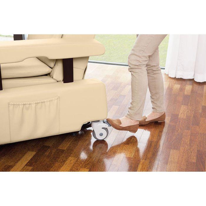 Eine Person mit braunen Schuhen stellt an einem weißen Sessel die Rollen ein. Der linke Fuß ist dabei auf der Justierung des Rades.