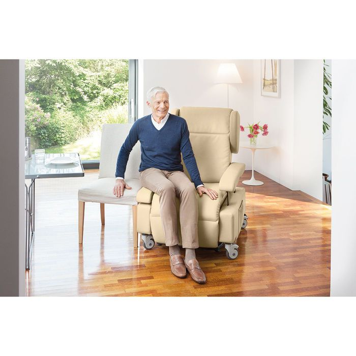 Ein älterer Mann mit blauen Pullover sitzt auf einem weißen Sessel mit Rollen. Seinen rechten Arm stützt er auf einem Stuhl ab, der direkt neben dem Sessel steht.