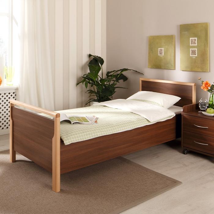 Braunes Bett mit Bettdecke und Kissen.