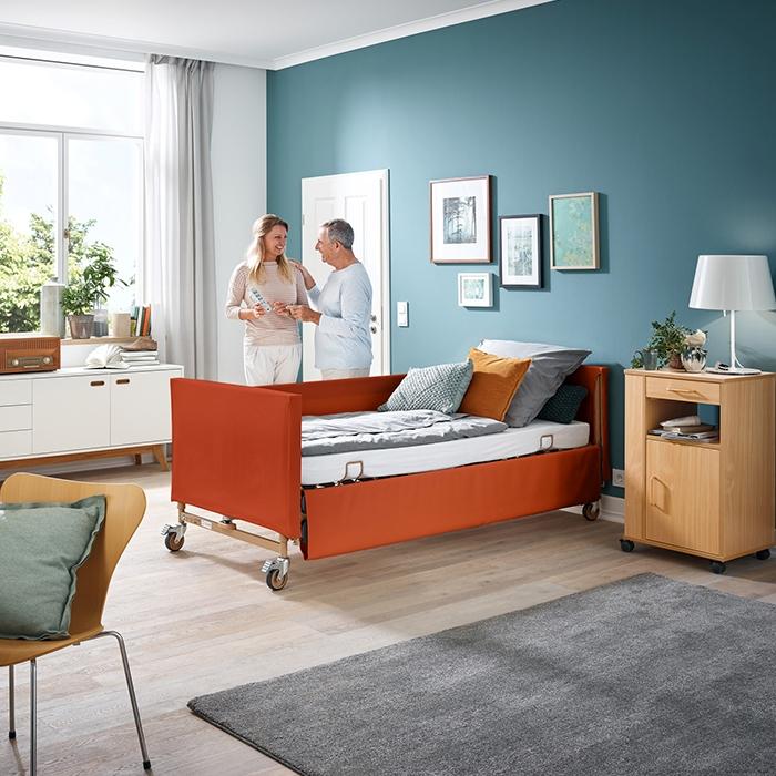 Mann und Frau stehen an einem Pflegebett