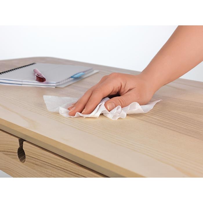 Hand wischt mit einem Desinfektionstuch über einen Holztisch.