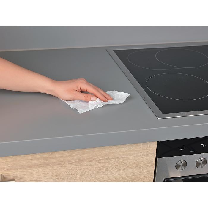 Hand wischt mit einem Desinfektionstuch über eine graue Küchenzeile.