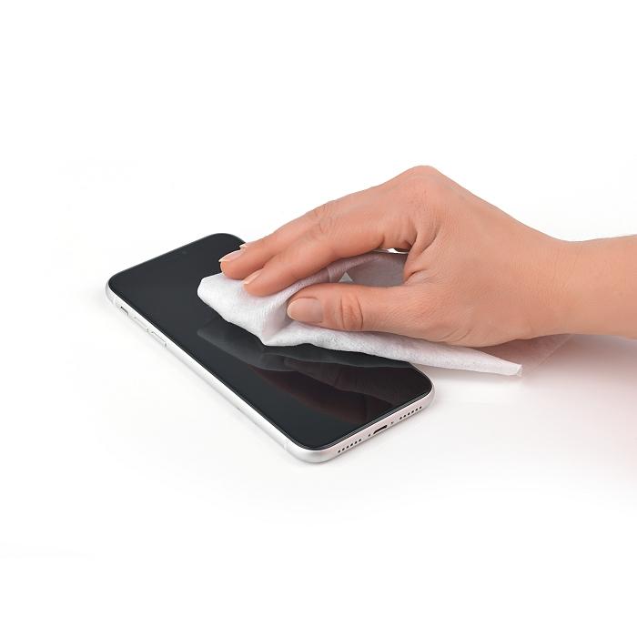 Hand wischt mit einem Desinfektionstuch über ein schwarzes Handy.