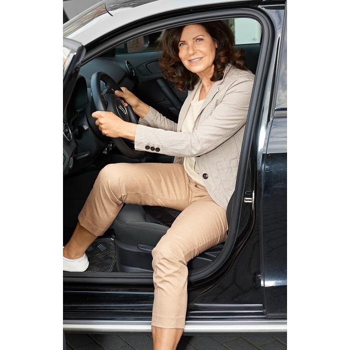 Eine Frau mit braunen Haaren steigt aus einem schwarzen Auto aus. Sie hält sich noch mit beiden Händen am Lenkrad fest.