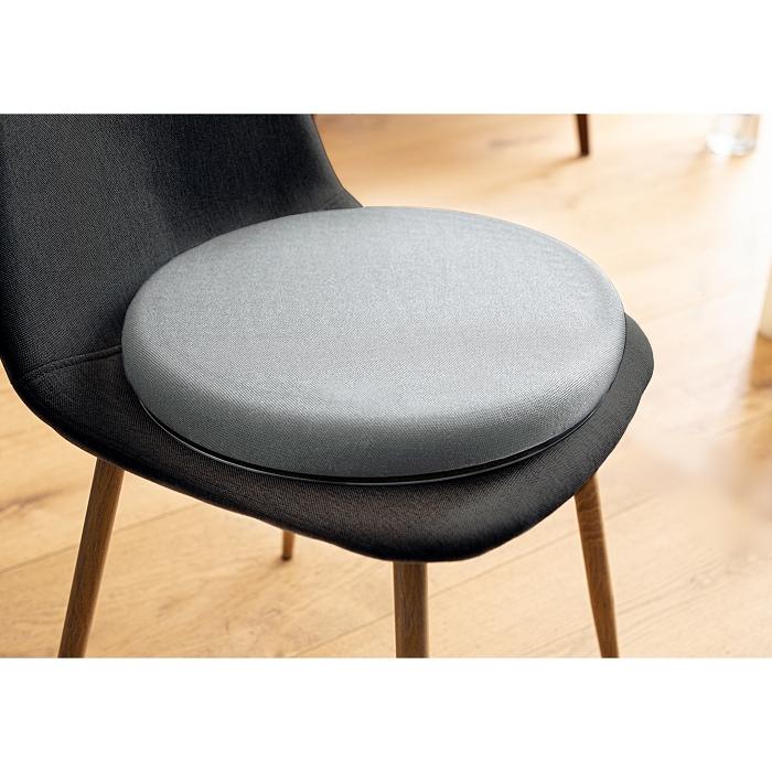 Ein rundes, graues Kissen liegt auf einem schwarzen Stuhl mit braunen Beinen.