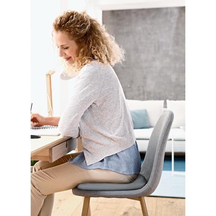 Eine Frau sitzt an einem Tisch auf einem runden Kissen.