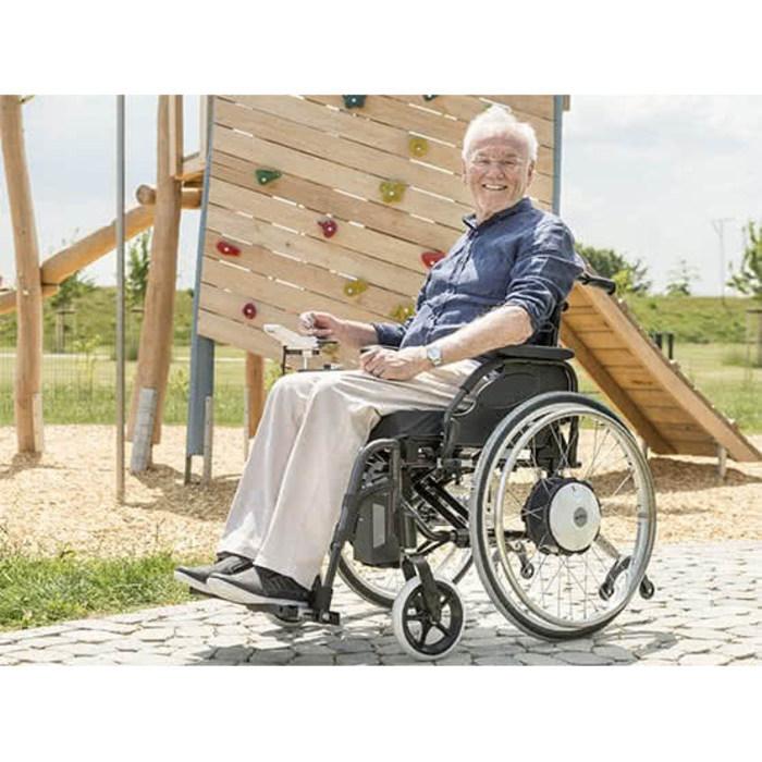 Ein Mann sitzt im Rollstuhl vor einem Spielplatz. Der Mann hat eine weiße Hose und ein blaues T-Shirt an.