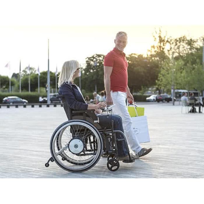 Zu sehen sind zwei Personen. Die eine Person sitzt in einem Rollstuhl und die andere Person steht daneben. Beide befinden sich draußen auf einem Platz in der Stadt.