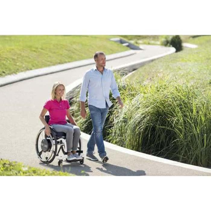Ein Mann und eine Frau sind auf einem Gehweg. Die Frau sitzt in einem Rollstuhl und der Mann läuft daneben. Neben dem Weg ist Gras zu sehen.