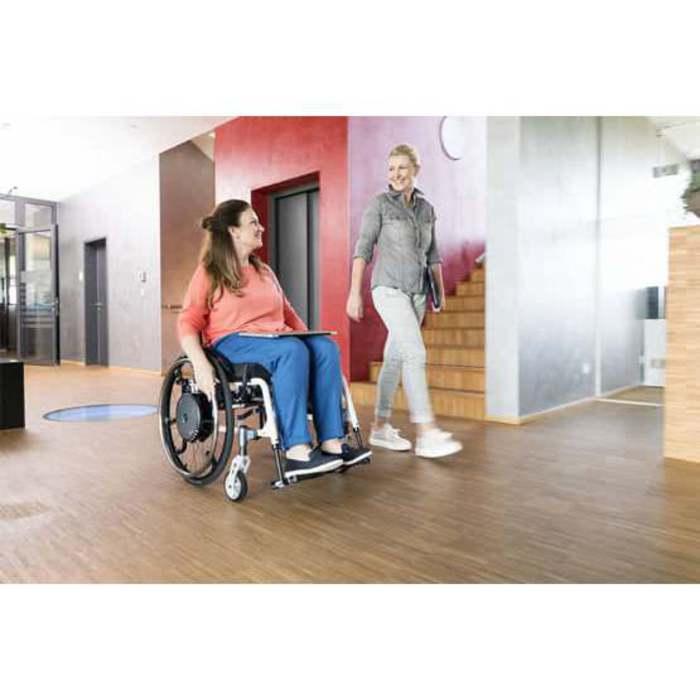 Zwei Frauen sind zu sehen die in einem Gebäude sind. Eine Frau sitzt in einem Rollstuhl und die andere Person läuft daneben.