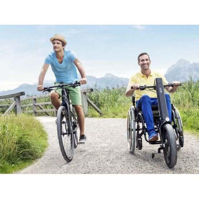 Zwei Personen gehen auf einem Weg. Die Frau fährt mit einem Fahrrad neben einem Mann der im Rollstuhl sitzt. Der Rollstuhl hat eine Zugmaschine.