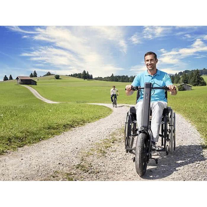 Eine Person mit einem hellblauen T-Shirt sitzt in einem Rollstuhl und fährt mit einer Zugmaschine auf einem Weg.