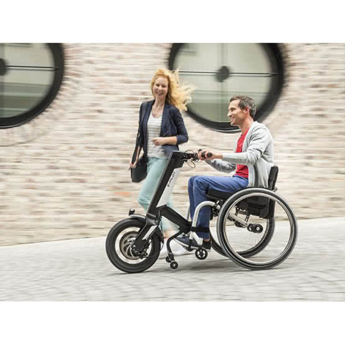 Zwei Personen gehen auf einem Weg. Die Frau läuft neben einem Mann der im Rollstuhl sitzt. Der Rollstuhl hat eine Zugmaschine.