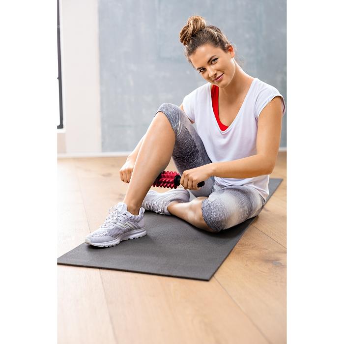 Eine Frau sitzt auf dem Boden auf einer Sportmatte. Mit beiden Händen hält sie eine Faszienrolle fest und rollt diese auf ihrer Wade.