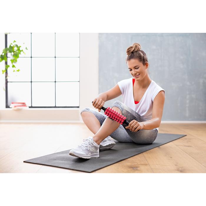 Eine Frau sitzt auf dem Boden auf einer Sportmatte. Mit beiden Händen hält sie eine Faszienrolle fest und rollt diese auf ihrem Schienbein.