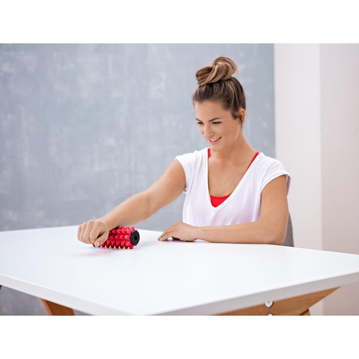 Eine Frau sitzt an einem Tisch und benutzt eine rote Faszienrolle für ihren Unterarm.