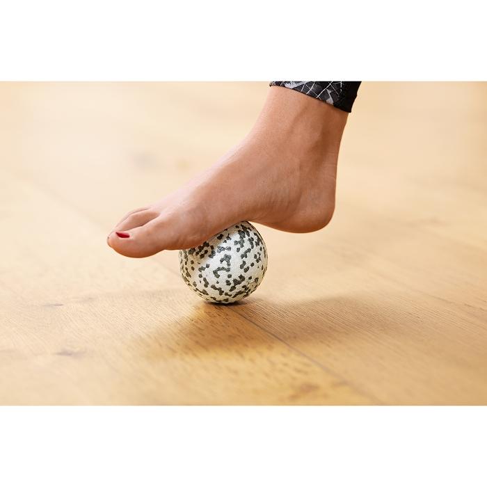 Eine Frau die mit ihrem Fuß eine Faszienrolle genutzt.