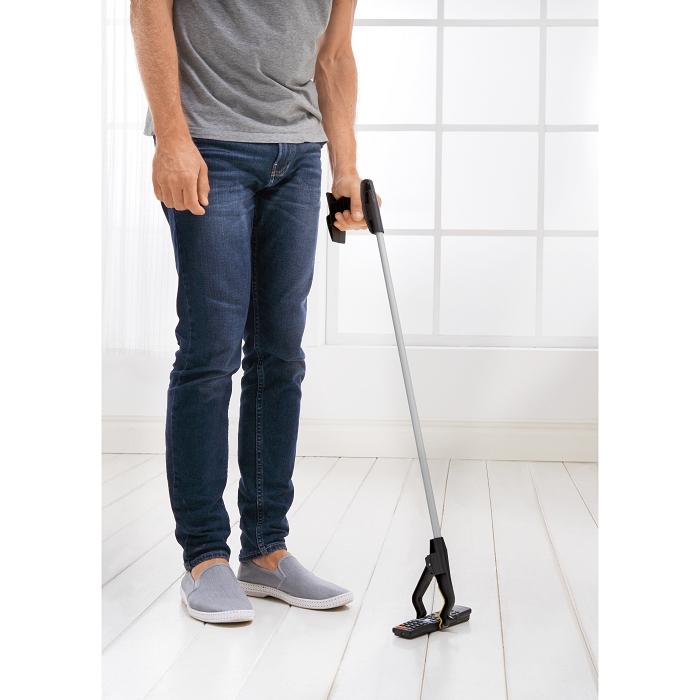 Eine Person die einen Gegenstand von einem gefliesten Boden aufhebt.