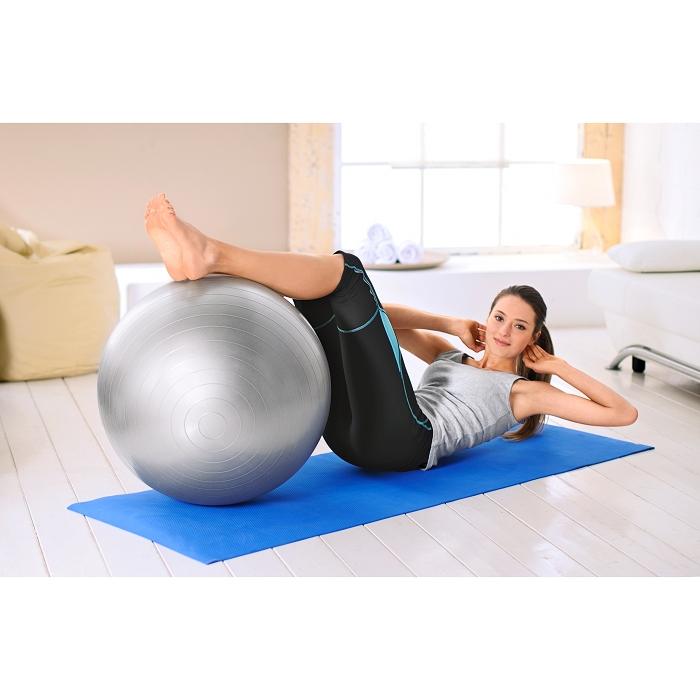 Eine Frau liegt auf dem Rücken auf einer Fitnessmatte. Unter ihren Beinen ist ein silberner Gymnastikball.