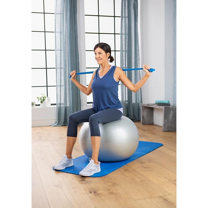 Eine Frau sitzt auf einem Gymnastikball und trainiert mit einem Gummiband.