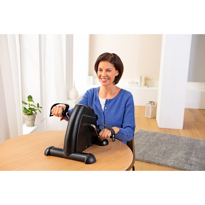 Eine ältere Frau sitzt an einem runden Holztisch. Vor ihr steht ein Heimtrainer, den sie mit ihren Händen bedient.