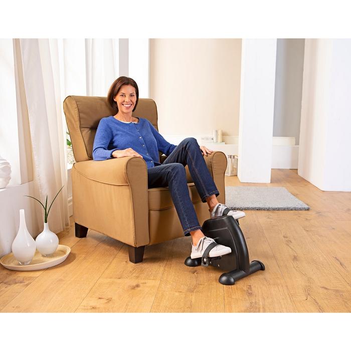 Ältere Frau sitz auf einem braunen Sessel. Mit ihren Füßen trainiert sie an einem Heimtrainer.