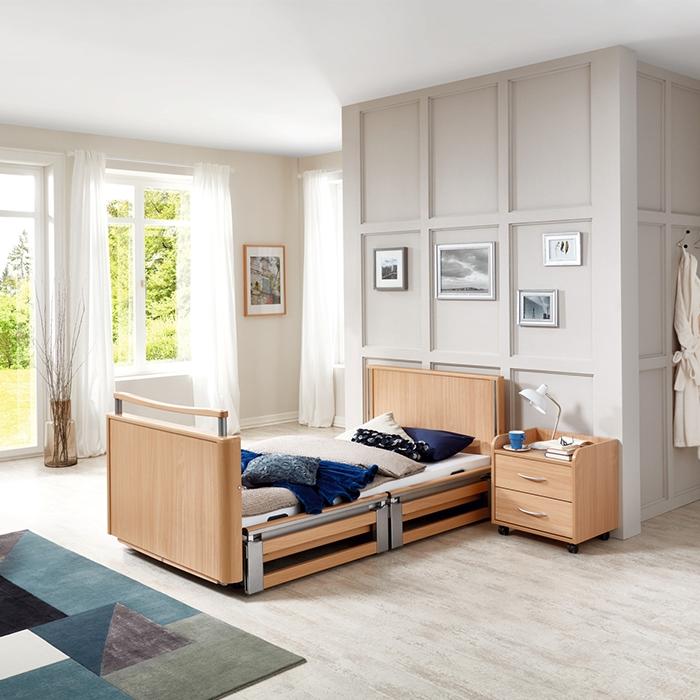 Pflegebett in Holzoptik steht in Raum.