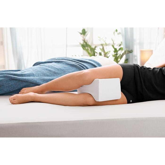 Eine Person liegt seitlich auf dem Bett. Diese benutzt ein Kniekissen.