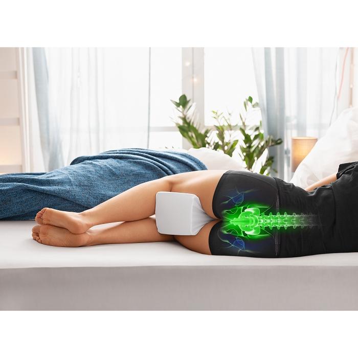 Eine Person liegt seitlich auf dem bett. Diese benutzt ein Kniekissen und eine Zeichnung ihres Rückens ist zu sehen, welche grün ist und den Rücken gerade zeigt.