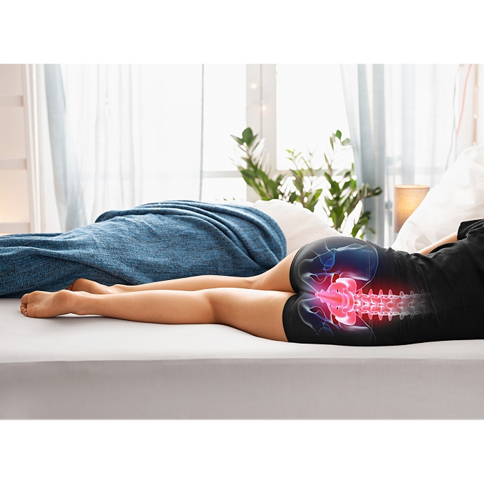 Eine Person liegt seitlich auf dem Bett. Diese benutzt kein Kniekissen und auf ihrem Rücken ist eine Zeichnung ihres Schiefen Rückens. Diese Zeichnung ist pink.