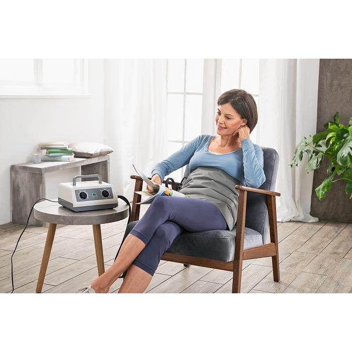 Eine Frau sitzt auf einem Stuhl und benutzt ein Massagegerät.