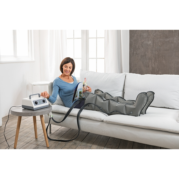 Eine Drau liegt auf einem weißen Sofa und hat ihre Beine in einem Massagegerät gewickelt.