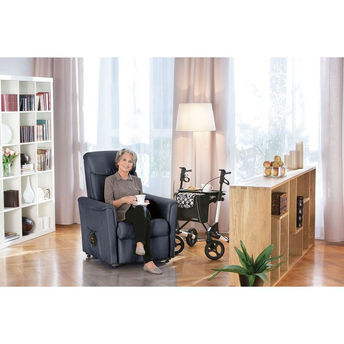 Eine ältere Frau sitzt auf einen titanfarbenden Sessel in einem Wohnzimmer. Neben ihr steht ein Rollator mit Essen drauf und in ihren Händen hält sie eine weiße Tasse. Die Frau guckt in die Kamera und grinst.