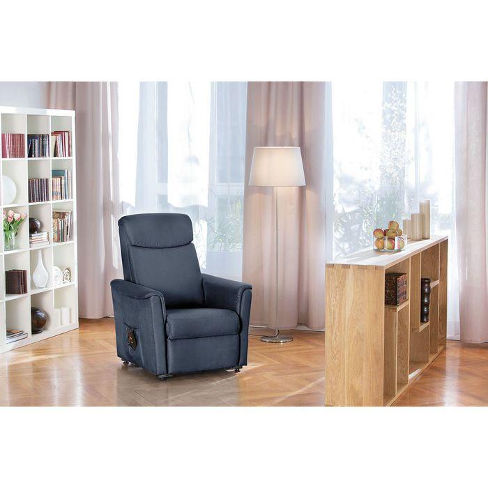 Ein titanfarbender Sessel in einem Wohnzimmer. Er steht relativ zentral. Ebenfalls ist ein Bücherregal und ein hüfthohes Holzregal zusehen.