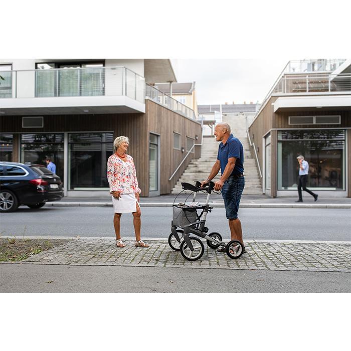 Ein Mann und eine Frau stehen an einer Straße und lachen. Der Mann stützt sich auf einem grauen Rollator ab.