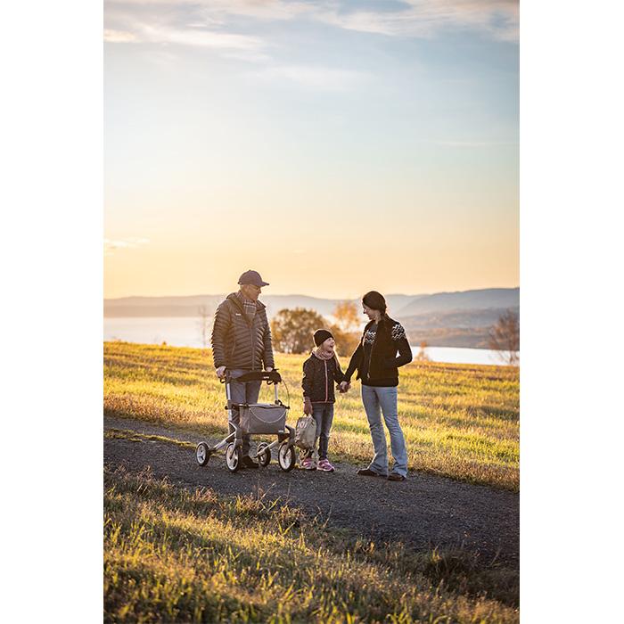 Eine dreiköpfige Familie läuft auf einem Weg. Das Kind und die Mutter halten händchen und der Mann stützt sich auf einem grauen Rollator ab.