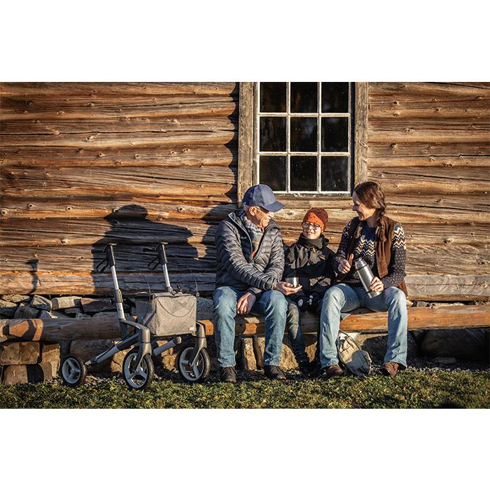 Eine dreiköpfige Familie sitzt vor einem Holzhaus. Die Frau hat eine Teekanne in der Hand und der ältere Mann hält einen Becher in ihre Richtung. In der Mitte sitzt ein Kind mit Brille. Neben dem älteren Mann steht ein Rollator.