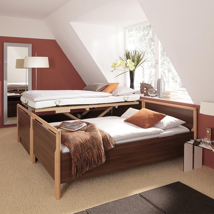 Zwei Betten nebeneinander, eines ist höhenverstellt.