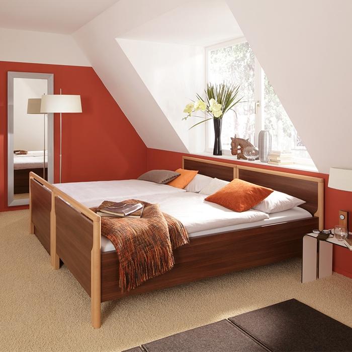 Zwei Betten nebeneinander vor einem Fenster.