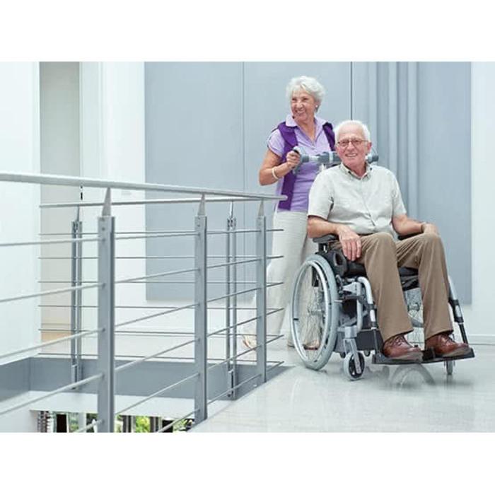 Eine ältere Frau schiebt den Rollstuhl eines älteren Mannes. Sie befinden sich auf einer Brücke eines Gebäudes.