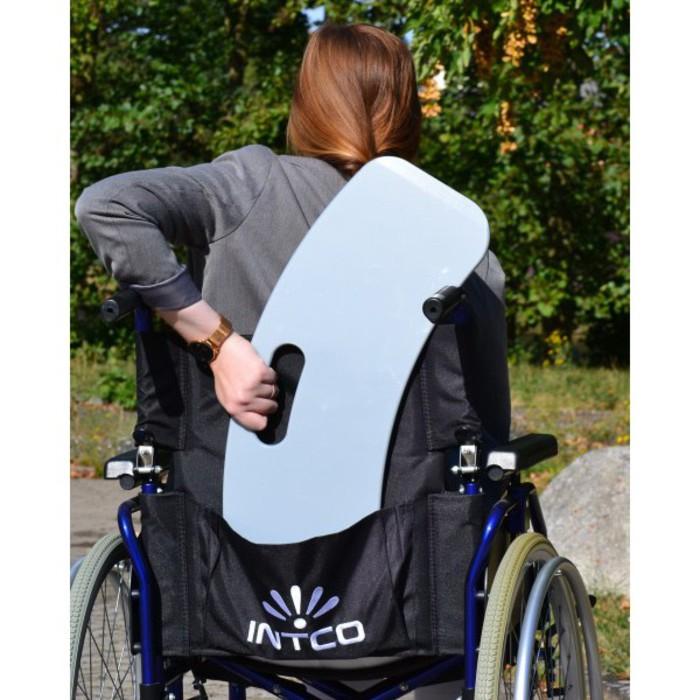 Eine Frau mit roten Haaren sitzt im Rollstuhl. Sie ist von hinten zu sehen und hat den Silber Gleiter in der Tasche vom Rollstuhl