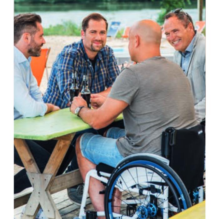 Ein weißer mittelalter Mann sitzt im Rollstuhl mit anderen Männern, die nicht im Rollstuhl sitzen, um einen Tisch im Freien.