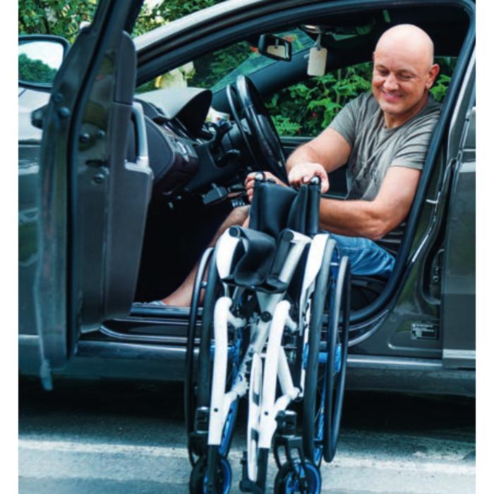 Ein weißer mittelalter Mann sitzt auf dem Fahrersitz eines dunklen Autos und faltet den Rollstuhl zusammen.